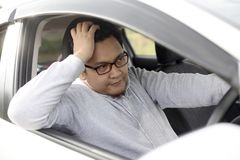 Male Driver Get Bored in His Car. Portrait of funny Asian male driver get bored in his car trapped in traffic jam, tired lazy facial expression gesture royalty free stock image