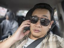 Male Driver Get Bored in His Car. Portrait of funny Asian male driver get bored in his car trapped in traffic jam, tired lazy facial expression gesture stock photos