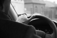 Male driver hands holding steering wheel.Driving safety in the city. background black and white Royalty Free Stock Photography