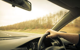 Male driver hands on steering wheel of a car and road Stock Photography