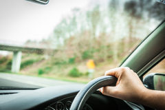 Male driver hands on steering wheel of a car and road. Male driver hands holding steering wheel of a car and road Royalty Free Stock Images
