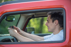 Male Driver Holding Cellphone by Wheels Stock Photos