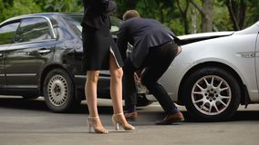 Male driver observing car damage, woman nervously walking, road accident. Stock footage stock footage