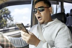 Male Driver Reading Message on  Smart Phone While Driving a Car royalty free stock images