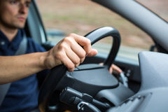 Male driver`s hands driving a car on a highway Royalty Free Stock Photography