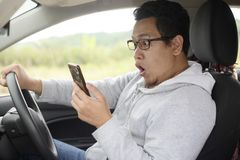 Male Driver Shocked to See His Phone. Portrait of Asian male driver shocked to see his phone, surprised in his car indonesian malaysian auto automobile vehicle royalty free stock photo