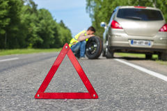Male driver with spare wheel on the roadside Royalty Free Stock Photography