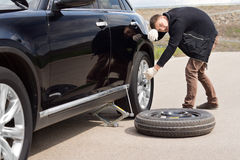 Male driver struggling to change his car tyre Royalty Free Stock Photography