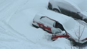 Male driver trying to free his car from snowy captivity. Parked cars covered with snow. Bad weather in town. Snowy day. Urban scene. Weather concept stock video footage