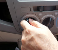 Male driver turning car air conditioner knob Royalty Free Stock Photos