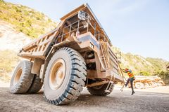 Male driver walks up the stairs of large quarry dump truck, production useful minerals, to transport coal from open pit in royalty free stock images