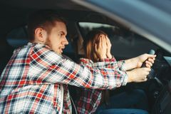 Driving Instructor helps driver to avoid accident. Male driving instructor helps the novice driver to avoid an accident, car school concept. Test for beginner stock photos