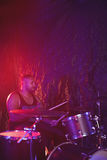 Male drummer performing in nightclub. Confident male drummer performing in nightclub Royalty Free Stock Photo