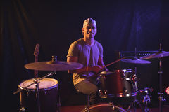Male drummer performing in nightclub. Portrait of male drummer performing in nightclub Royalty Free Stock Image