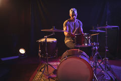 Male drummer performing in nightclub. Serious male drummer performing in nightclub Royalty Free Stock Photos
