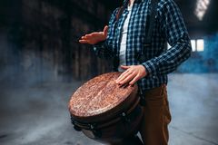 Male drummer playing on wooden drum. Musician in motion. Bongo, musical percussion instrument, ethnic music Royalty Free Stock Photo