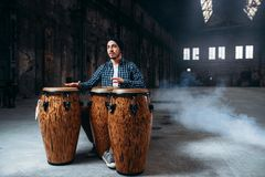 Male drummer plays on wooden drums in factory shop. Musician in motion. Bongo, musical percussion instrument, ethnic music Stock Images