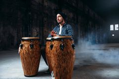 Male drummer plays on wooden drums in factory shop. Musician in motion. Bongo, musical percussion instrument, ethnic music Royalty Free Stock Images