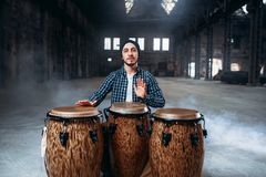 Male drummer plays on wooden drums in factory shop. Musician in motion. Bongo, musical percussion instrument, ethnic music Royalty Free Stock Photo