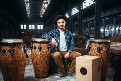 Male drummer pose against african wooden drum. Young male drummer pose against african wooden drum, factory shop on background. Djembe, musical percussion Royalty Free Stock Photos