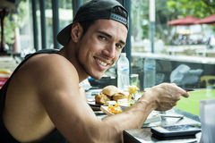 Male eating in cafe. Handsome young man having meal in cafe Royalty Free Stock Photography