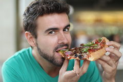 Male eating a yummy slice of fresh pizza.  Stock Photo