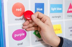 An educator explains the spelling of the word red. A male educator explains the spelling of the word red on the training table in the training room Royalty Free Stock Photography