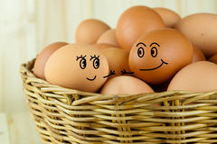 Male egg and female egg going to hold their hands in a wicker basket in wood background. Male egg and female egg going to hold their hands in a wicker basket in Royalty Free Stock Image