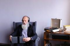 Male Elderly person enjoys listening to rock music on headphones royalty free stock photo