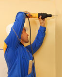 Male with electric drill making hole in wall Royalty Free Stock Images