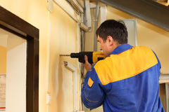 Male with electric drill making hole in wall Royalty Free Stock Photos