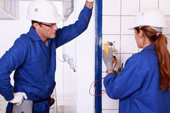 Male electrician and female apprentice Royalty Free Stock Images