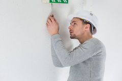 Male electrician fixing electric sign on ceiling Stock Photo