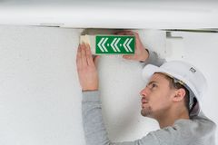 Male electrician fixing electric sign on ceiling. A male electrician fixing electric sign on the ceiling Stock Photos