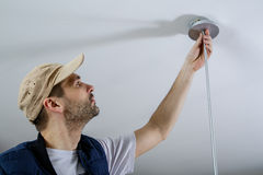 A male electrician fixing light on the ceiling. Close-up Stock Images