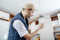 A male electrician fixing light on the ceiling. Worker changing a light bulb in the kitchen. Close-up Stock Images
