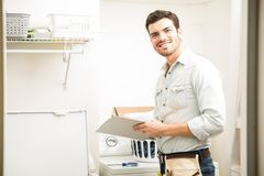 Male electrician fixing a washer Royalty Free Stock Photography