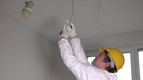 Male electrician installing fire smoke alarm with screwdriver stock footage