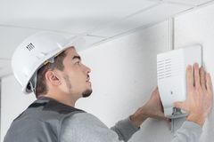 Male electrician installing security system door sensor on wall. Technician stock photo