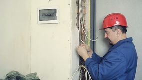Male electrician performs installation work. Male electrician working on laying the cable in the apartment. Installation of electrical wires stock footage