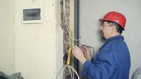 Male electrician performs installation work. Male electrician working on laying the cable in the apartment. Man carries out measurement of electrical signals in stock footage