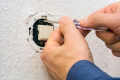 Male electrician repairing electric switch. With screwdriver on white wall Royalty Free Stock Photo