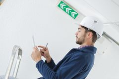 Male electrician standing on stepladder repairing light. Male Royalty Free Stock Images