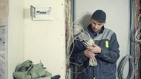 Male electrician performs installation work. Male electrician working on laying the cable in the apartment. Installation of electrical wires stock video