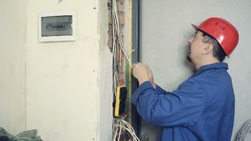 Male electrician performs installation work. Male electrician working on laying the cable in the apartment. Man carries out measurement of electrical signals in stock video footage