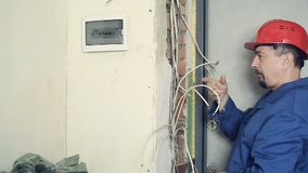 Man electrician performs installation work. Male electrician working on laying the cable in the apartment. The person carries out installation of electric wires stock video