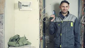 Male electrician performs installation work. Male electrician working on laying the cable in the apartment. A person gets a finger injury when working with a stock video footage
