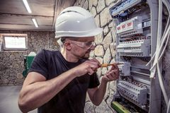 A male electrician works in a switchboard with an electrical con. Necting cable, connects the equipment with tools, the concept of complex work, space for text Royalty Free Stock Images
