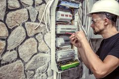 A male electrician works in a switchboard with an electrical con. Necting cable, connects the equipment with tools, the concept of complex work, space for text Royalty Free Stock Photos