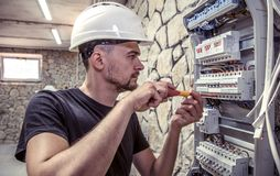 A male electrician works in a switchboard with an electrical con. Necting cable, connects the equipment with tools, the concept of complex work, space for text Stock Photo